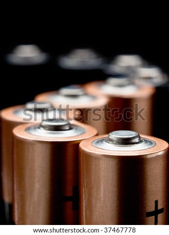 batteries in a S-shaped column , macro photo over black background, useful for various conceptual energy related purposes