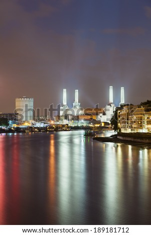 Battersea Power Station in London at night with the Thames River in the foreground - stock photo