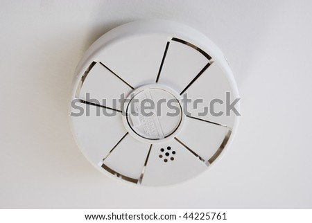 Battery operated smoke detector on ceiling.  Horizontally framed shot.