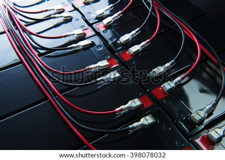 Battery powered. Industrial battery hooked up in parallel with long red and black cable bundles, coming from the terminal. Focus on center connector. Shallow depth of field. - stock photo