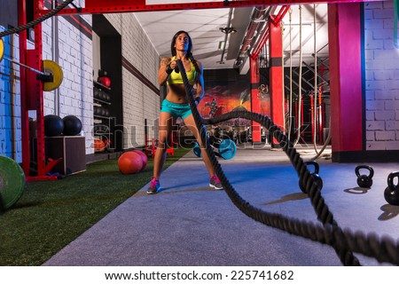 battling ropes girl at gym workout exercise fitted body - stock photo