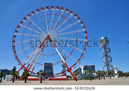 BATUMI, GEORGIA - CIRCA MAY 2013: Ferris wheel and Alphabetic Tower in Batumi circa May 2013. Two helix bands rise along the tower holding 33 letters of the Georgian unique alphabet.