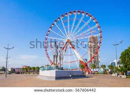 "BATUMI, GEORGIA - SEPTEMBER 22, 2015: Moving metal sculpture ""Ali and Nino"" (old name ""Man and Woman"") by Tamara Kvesitadze and Ferris wheel in Batumi, Georgia."