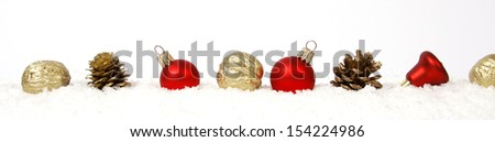 Baubles nuts and cones on the white snow - stock photo