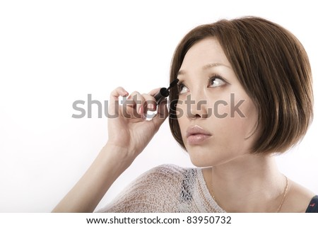 Bautiful asian woman applying mascara