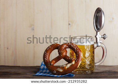 bavarian beer and a pretzel on wood  - stock photo