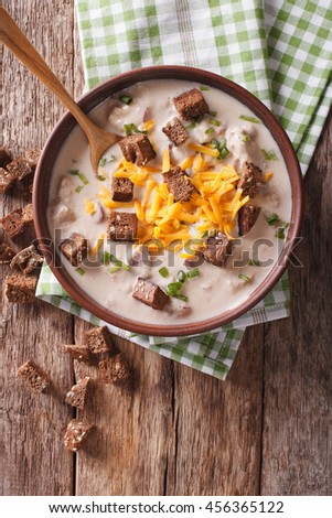 Bavarian beer soup with cheese and bacon close up in a bowl on the table. Vertical view from above - stock photo