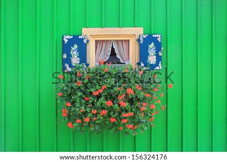 bavarian boathouse with green Panels, and decorative small window with geranium flowers and painted shutters - stock photo