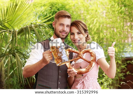 Bavarian couple in traditional costume with beer and brezel outdoor in a beergarden