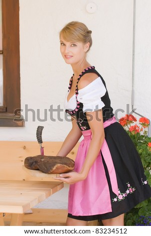 Bavarian Dirndl woman serving a bacon on a plate Alm /Bavarian woman in a dirndl