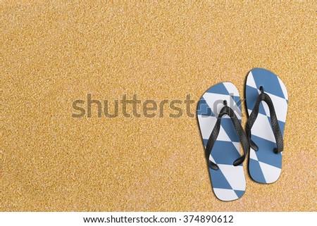 Bavarian flip flips on sand for background - stock photo