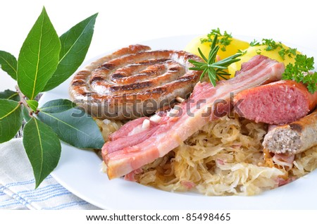 Bavarian fresh belly of pork and sausages on sauerkraut with potatoes