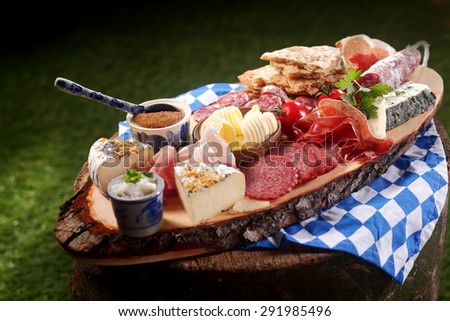 Bavarian Gourmet meat and cheese platter with assorted spicy sausages, ham, and salami with a variety of cheeses, sauce and butter served outdoors on a rustic tree stump in the sunshine - stock photo