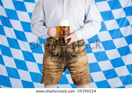 Bavarian man with Oktoberfest beer stein (Mass) and leather pants (Lederhose). In background is Bavarian flag visible. - stock photo
