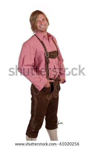 Bavarian man with oktoberfest leather trousers (lederhose) holds suspenders. Isolated on white background. - stock photo