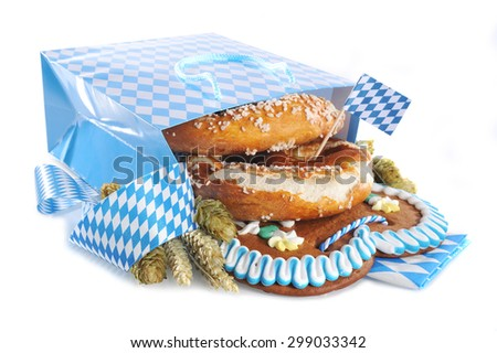 Bavarian Oktoberfest paper shopping bag with gingerbread heart, soft pretzel, hops and wheat from Germany  - stock photo