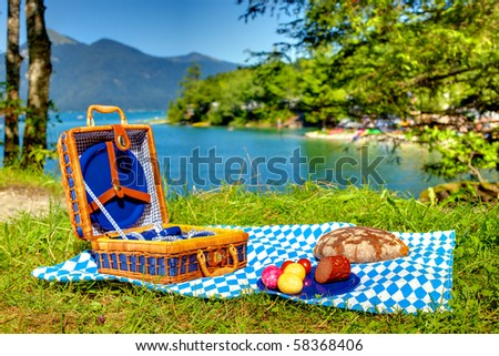 bavarian striped picnic cloth with basket and food on it