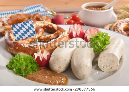 Bavarian veal sausage breakfast with sausages, soft pretzel and mild mustard on dark weathered wooden board - stock photo