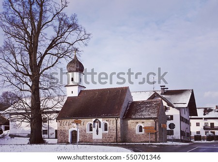Bavarian winter landscape with snow, crossroad and ancient chapel with onion dome