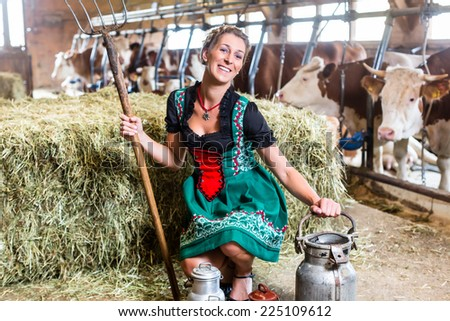 Bavarian woman with sexy Dirndl dress, milk can and pitchfork in cow house - stock photo