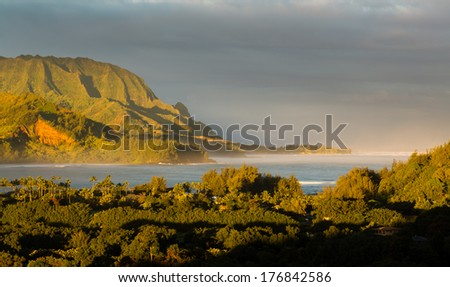 Bay at Hanalei in Kauai with the Na Pali mountain range in the background. Taken just after dawn with the rising sun lighting the peaks of the mountains and casting a sunbeam ray into the ocean - stock photo