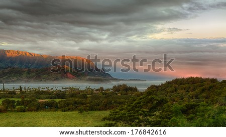 Bay at Hanalei in Kauai with the Na Pali mountain range in the background. Taken just after dawn with the rising sun skimming the peaks of the mountains and casting a sunbeam ray into the ocean - stock photo