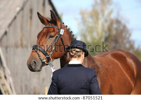 Bay horse portrait and its owner - stock photo