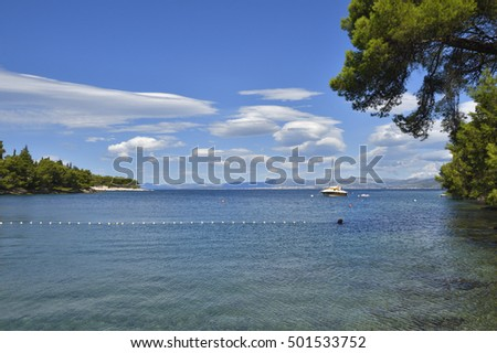 Bay in adriatic sea on Brac Island in Croatia with clear water and blue sky and a boat in background.