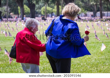 Bay Pines, Florida - may 26 : family members give their respects to deceased friends and loved ones on memorial day at the VA cemetery, may 26 2014 in Bay Pines VA cemetery in Florida