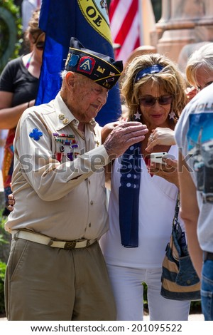 Bay Pines, Florida - May 26 : Veteran and family members looking at a smart phone after the Memorial Day parade, May 26 2014 in Bay Pines VA cemetery in Florida