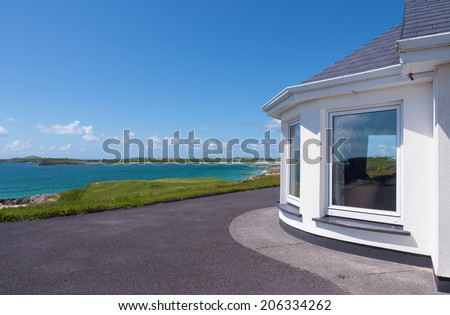 Bay window of a white beach house in Connemara, Ireland, with the Atlantic Ocean in the background. - stock photo