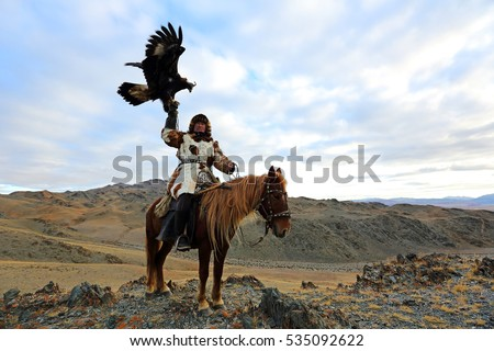 BAYAN-ULGII, MONGOLIA - SEP 25: A senior mongolian horseman in traditional kazakh clothing with his altai golden eagle of village sagsai on September 25, 2016 in Bayan-Ulgii, Mongolia