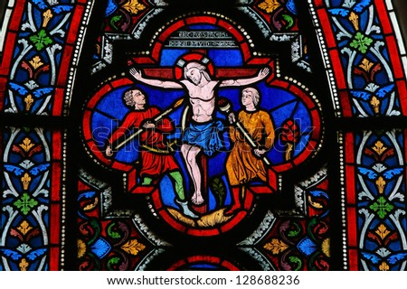 BAYEUX - FEBRUARY 12: Stained glass window depicting Jesus on the Cross in the cathedral of Bayeux, Normandy, France,  on February 12, 2013. - stock photo