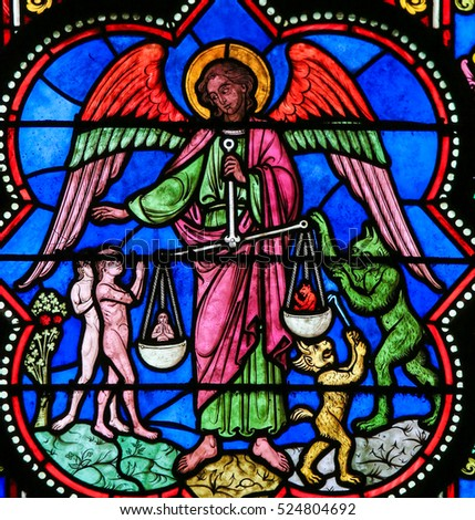BAYEUX, FRANCE - FEBRUARY 12, 2013: Stained Glass window in the Cathedral of Bayeux, France, depicting the Archangel Michael holding a set of scales, performing the Divine Measure of Souls