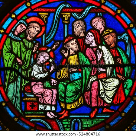 BAYEUX, FRANCE - FEBRUARY 12, 2013: Stained Glass window in the Cathedral of Bayeux, France, depicting Christ among the Doctors in the Temple in Jerusalem