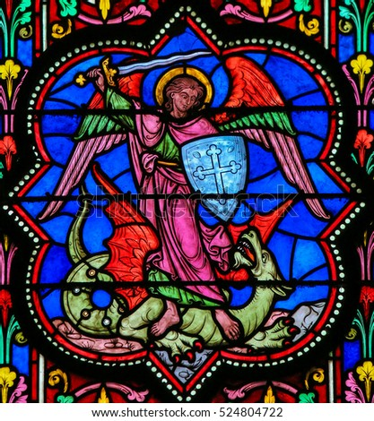 BAYEUX, FRANCE - FEBRUARY 12, 2013: Stained Glass window in the Cathedral of Bayeux, France, depicting the Archangel Michael slaying Satan, a Dragon.