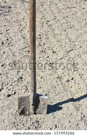 Bayonet shovel with wooden handle stuck into the ground