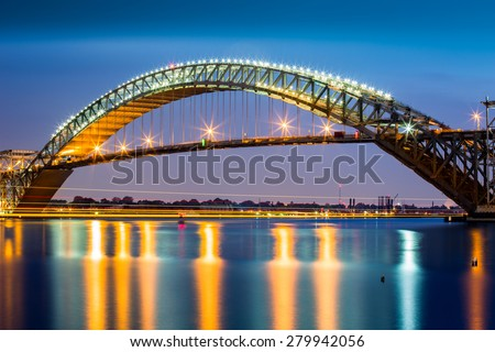 Bayonne Bridge at dusk. The Bayonne Bridge, is the 5th longest steel arch bridge in the world, spans the Kill Van Kull and connects Bayonne, NJ with Staten Island, NY - stock photo