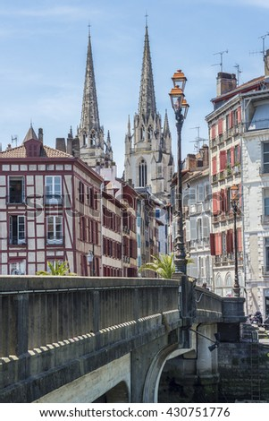 Bayonne, France - May 21, 2016: Pont Marengo bridge over Le Nive river with the Cathedral of Sainte-Marie de Bayonne, in background. View from Quai des Corsaires. Aquitaine,  France.