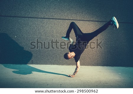BBoy doing handstand on street - stock photo