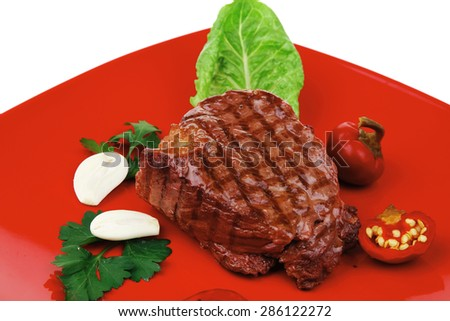 bbq : beef (pork) steak garnished with green lettuce and red chili hot pepper on red plate isolated over white background - stock photo