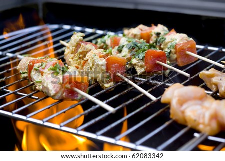 BBQ chicken kebabs on grill with flames - stock photo