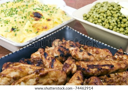 BBQ chicken with scalloped potatoes and peas.
