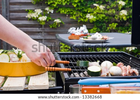 BBQ cooking. Placing the material on a grate above the coal. - stock photo
