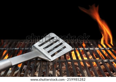 BBQ Grill And Spatula. Flame Of Fire In The Background. - stock photo