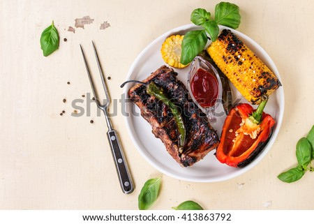 BBQ grilled pork ribs, corn, green chili and red bell pepper, served in white ceramic plate with barbecue sauce, fresh basil and meat fork over white wooden background. Flat lay - stock photo