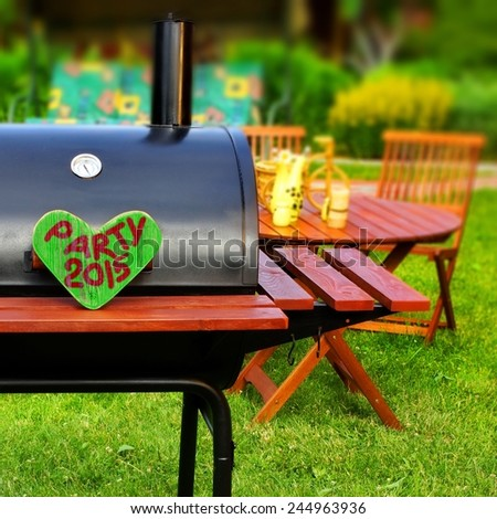 BBQ Party 2015 Sign on Wooden Heart at Barbecue Appliance on the Backyard at Summertime. Outdoors Furniture on the background. - stock photo