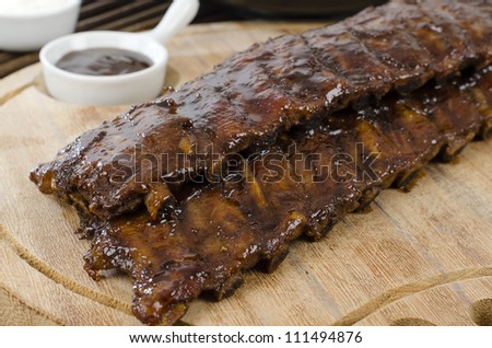 BBQ Ribs - Marinated pork ribs with barbeque sauce dip. - stock photo