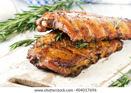 BBQ ribs  on a wooden cutting board. Selective focus - stock photo