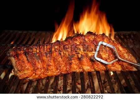 BBQ Roast Marinated Baby Back Pork Ribs Close-up On Hot Flaming Grill Background - stock photo